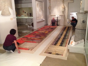 Conservators from ICA Art Conservation prepare to reinstall a watercolor panel.