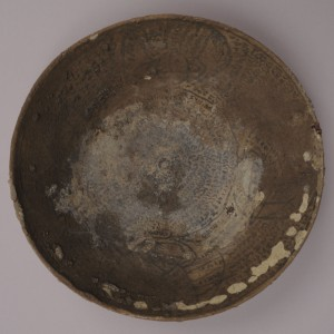 Incantation bowl (KM 31455) from the site of Seleucia-on-the-Tigris.   The object is a wheel-thrown, buff-colored earthenware bowl the surface of which has been painted with black pseudoscript (small lines meant to mimic Aramaic writing) and images of anthropomorphic figures.