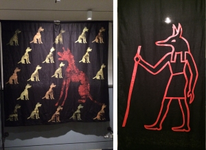 "The ""Death Dogs"" exhibition includes banners inspired by (left) representations of dogs found on ancient stelae from Terenouthis, Egypt, and (right) an Egyptian hieroglyph of a jackal god."