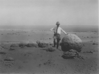 """Image KS175_04: April 27, 1920; George R. Swain; Dimay trip. """"Dr. Askren standing by a spherical boulder, on the way from the lake to Dimay."""""""