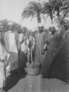 """Image KS175_09: April 28, 1920; George R. Swain; """"Man with string of fish, with several native bystanders. At El Lahoun station."""""""