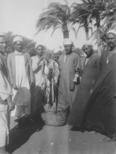 "Image KS175_09: April 28, 1920; George R. Swain; ""Man with string of fish, with several native bystanders. At El Lahoun station."""