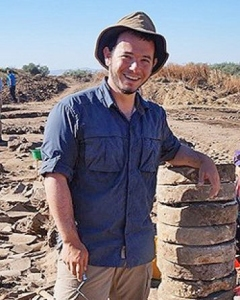 Man in blue shirt among ancient ruins.