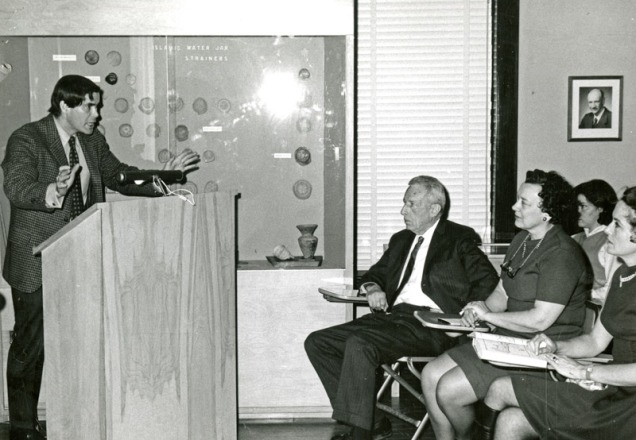 photo of man at podium in front of seated audience.