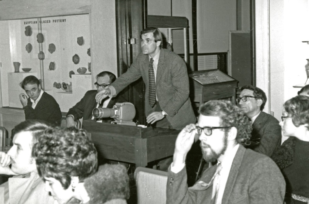 man in suit handles a slide projector while seated audience members look on.