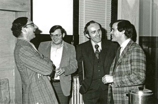 four men in suits laughing.
