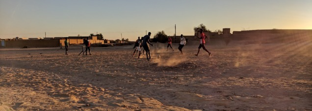boys playing soccer on a dirt field