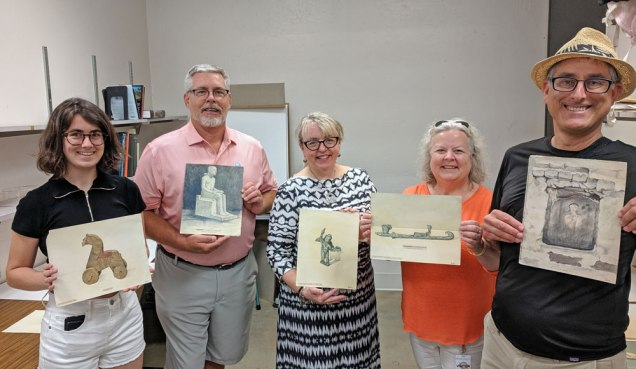 five people holding drawings