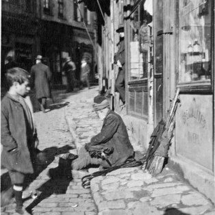"""The umbrella mender sitting on the sidewalk on a typical street."" KS043.04."