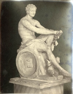 statue of a seated Apollo with baby Cupid at his feet.