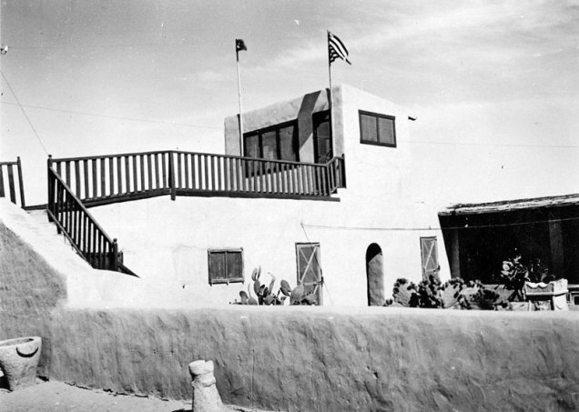 mudbrick house with flags