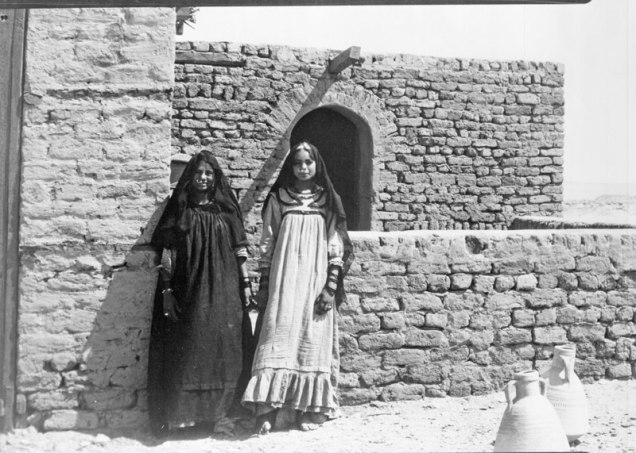 two young girls standing near a wall